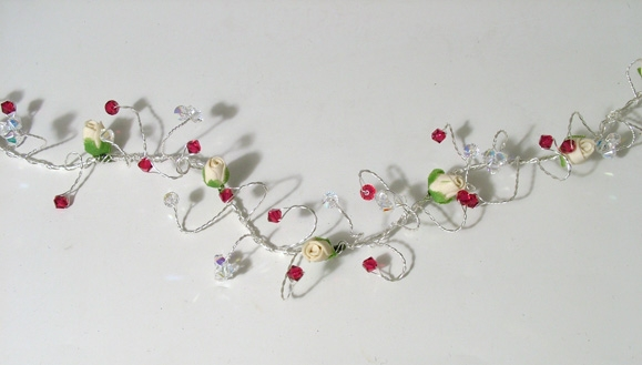 Winter wedding hair vine with white flower buds and ruby red crystals.